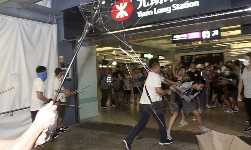 In this Sunday, July 21, 2019, photo, men in white shirts armed with metal rods and wooden poles attack commuters at a subway station in New Territory in Hong Kong. — Apple Daily via AP