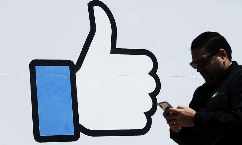In this April 25, 2019, photo a man walks past the thumbs up Like logo on a sign at Facebook headquarters in Menlo Park, Calif. — AP