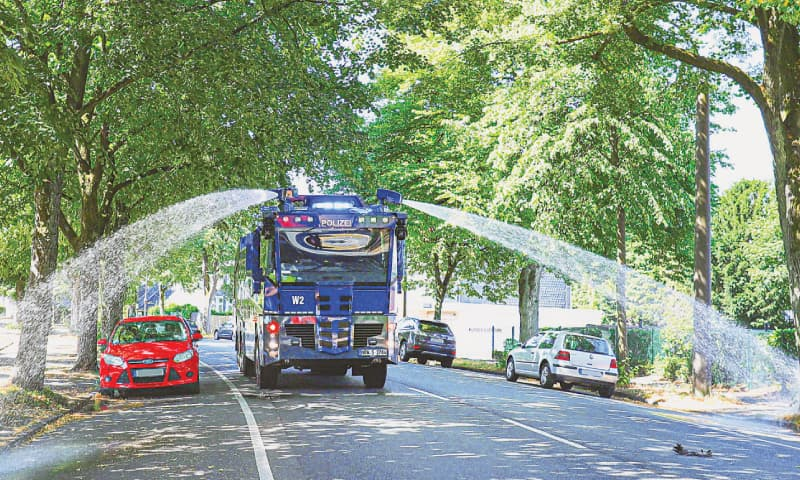 Police use water cannon to irrigate roadside trees in Wuppertal, Germany. — Agencies