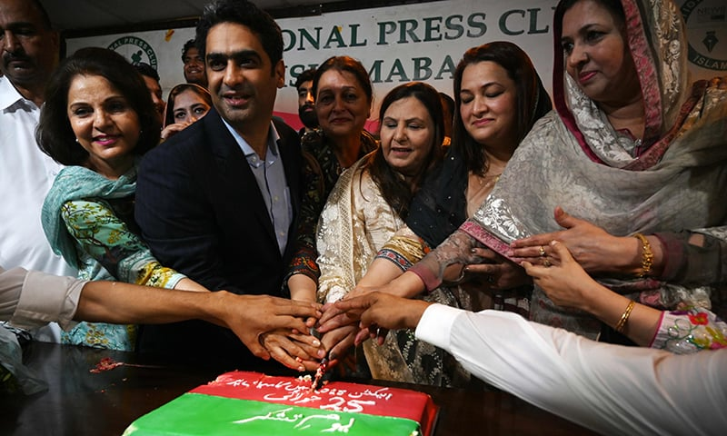 "PTI supporters cut a cake in Islamabad on July 25 to celebrate ""Thanks Giving Day"". — AFP"
