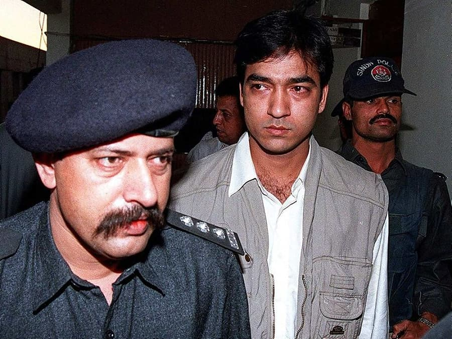 In this file photo taken on December 11, 1998, Pakistani police officer Chaudry Aslam (L) escorts Saulat Mirza (C), a suspect in the murder of six US nationals and numerous killings, in Karachi