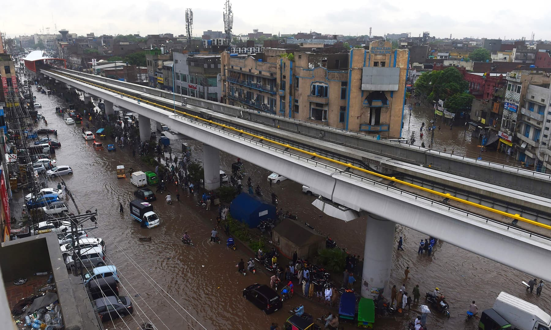 Pakistani commuters and pedestrians cross a flooded street after heavy monsoon rains in Lahore on July 16, 2019. - In Pakistan-administered Kashmir, officials said at least 23 people were killed after heavy rain triggered flash floods and damaged more than 120 houses and 30 shops, while crippling the water and electricity supplies. (Photo by ARIF ALI / AFP) — AFP or licensors