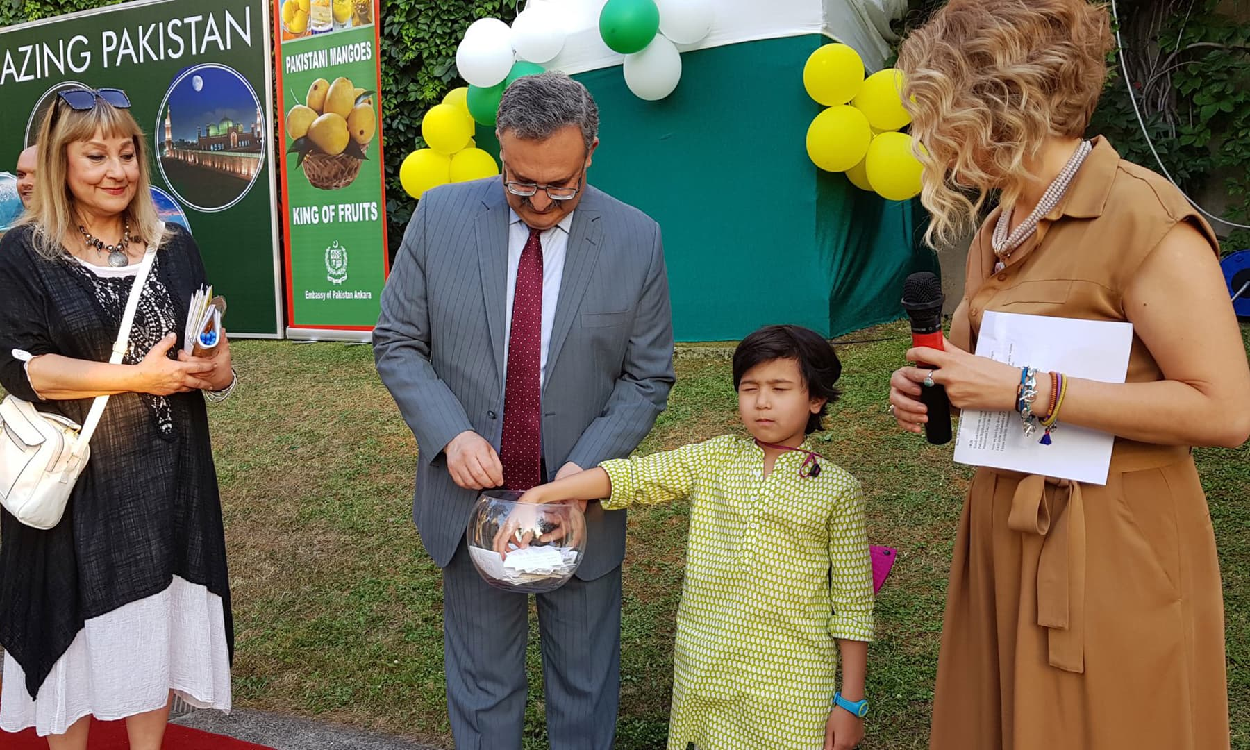 A young boy picks out a token in the lucky draw.