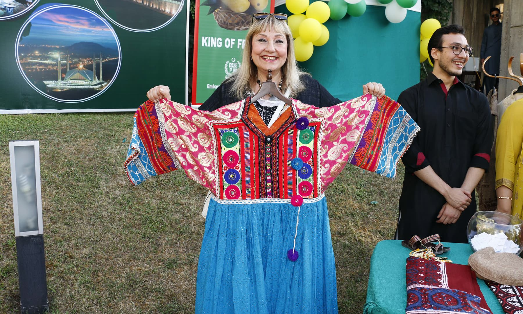 A woman posing with traditional, embroidered Pakistani attire.