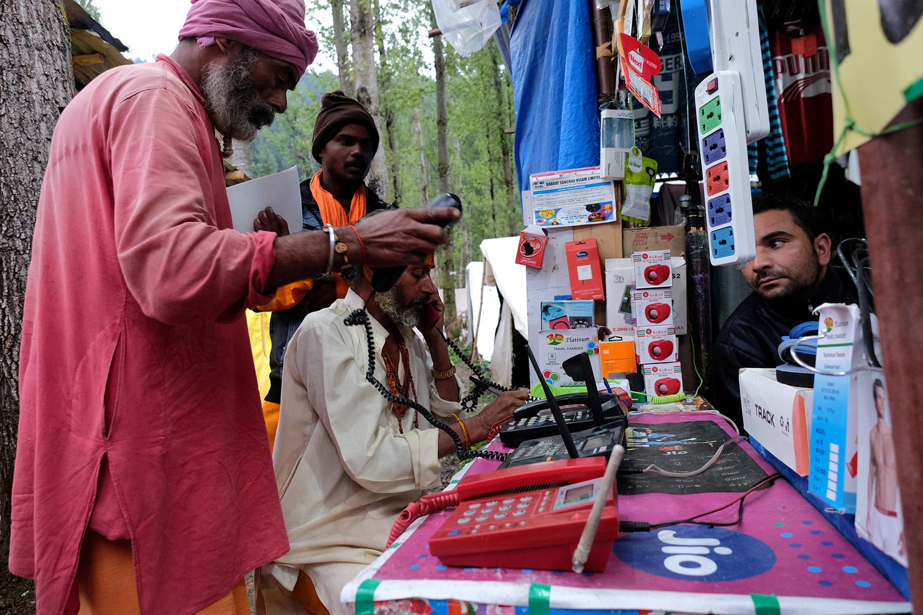 Hindu pilgrims make calls at a stall run by a Kashmiri Muslim before their journey towards the holy cave of Amarnath, where they worship an ice stalagmite that Hindus believe to be a symbol of Lord Shiva, at a base camp near Pahalgam in Indian-occupied Kashmir on July 26. — Reuters