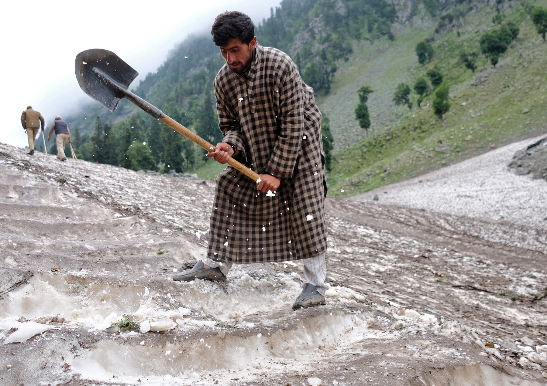 A Kashmiri man cuts snow to make way for Hindu pilgrims to trek to reach the holy Amarnath cave shrine, where they worship an ice stalagmite that Hindus believe to be the symbol of Lord Shiva, near Pahalgam in Indian-occupied Kashmir on July 27. — Reuters