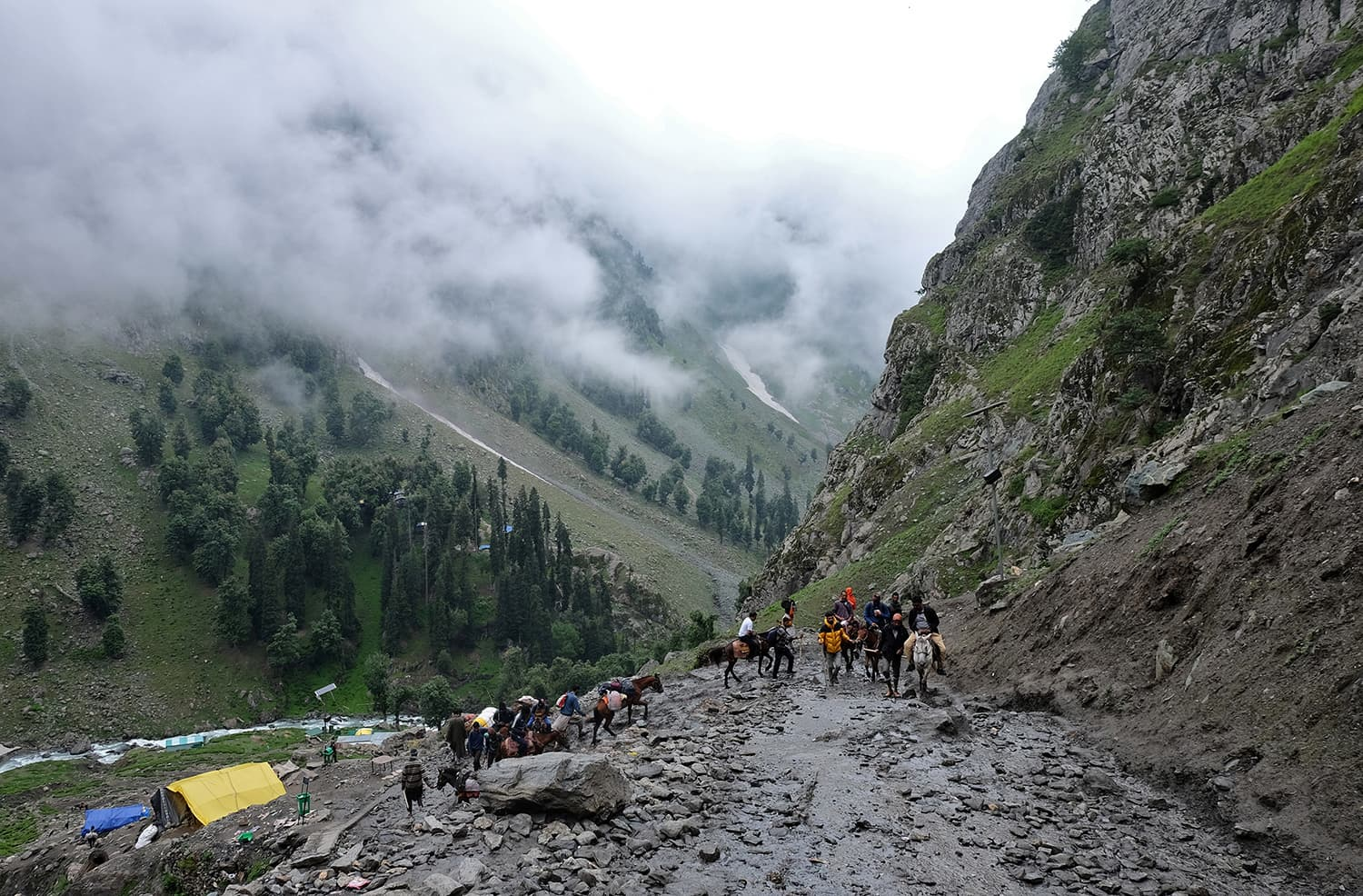 Hindu pilgrims trek through mountains to reach the holy Amarnath cave shrine, where they worship an ice stalagmite that Hindus believe to be the symbol of Lord Shiva, near Pahalgam  in Indian-occupied Kashmir on July 27. — Reuters