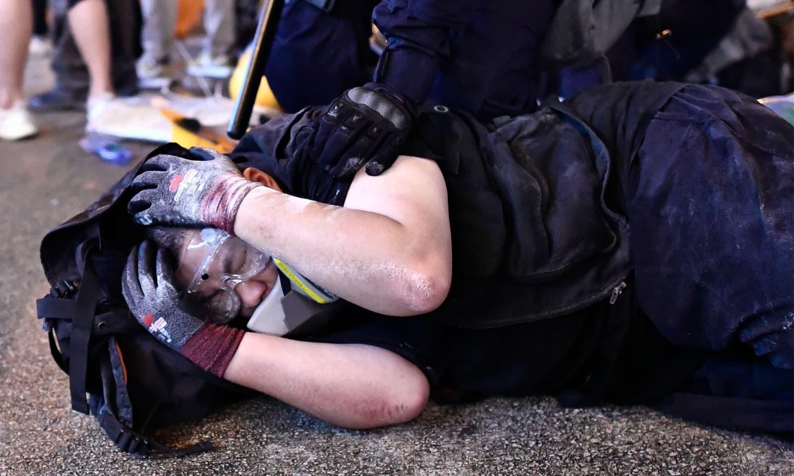 مظاہرے میں شریک ایک شخص کو پولیس نے دبوچ لیا—فوٹو: اے ایف پی