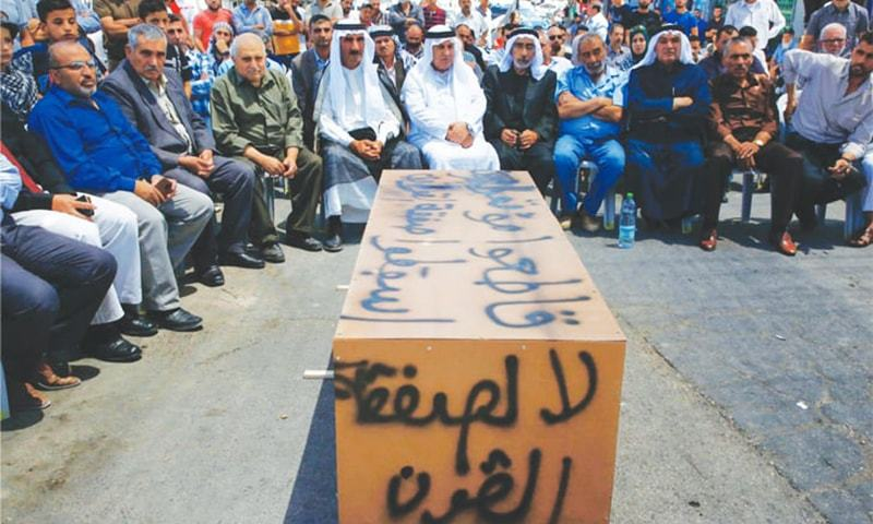 """In this file photo,  Palestinian men sit around a makeshift coffin with the words,  """"No to the deal of the century"""", during a protest in June against a US-led meeting in Bahrain. — AFP"""