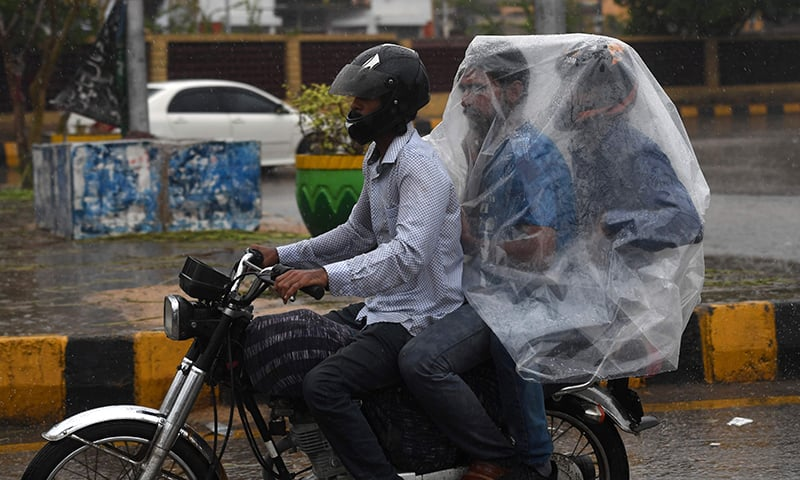 A Pakistani motorcyclist rides on a street as their passengers try to keep dry under plastic covering during monsoon rain in Karachi on July 29. — AFP
