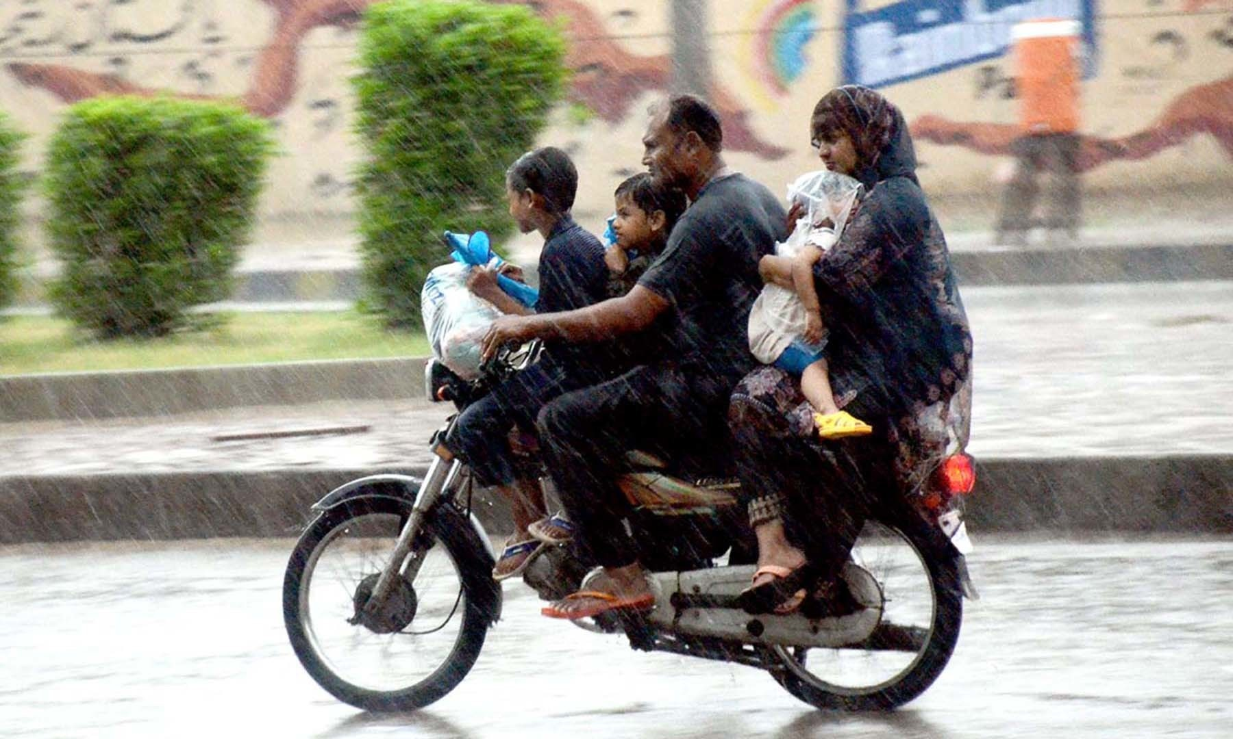A motorcyclist is pictured along with his family members on a street in Karachi on Monday. — APP