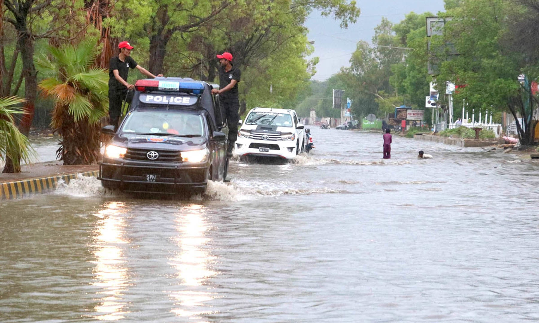 Vehicles pass through stagnant water accumulated after heavy rain in Hyderabad on Monday. — APP