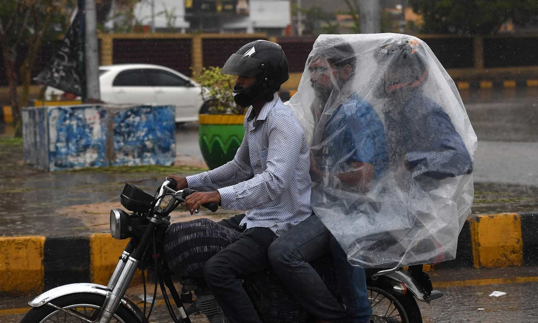 A motorcyclist rides on a street as their passengers try to keep dry under a plastic covering in Karachi on Monday. — AFP