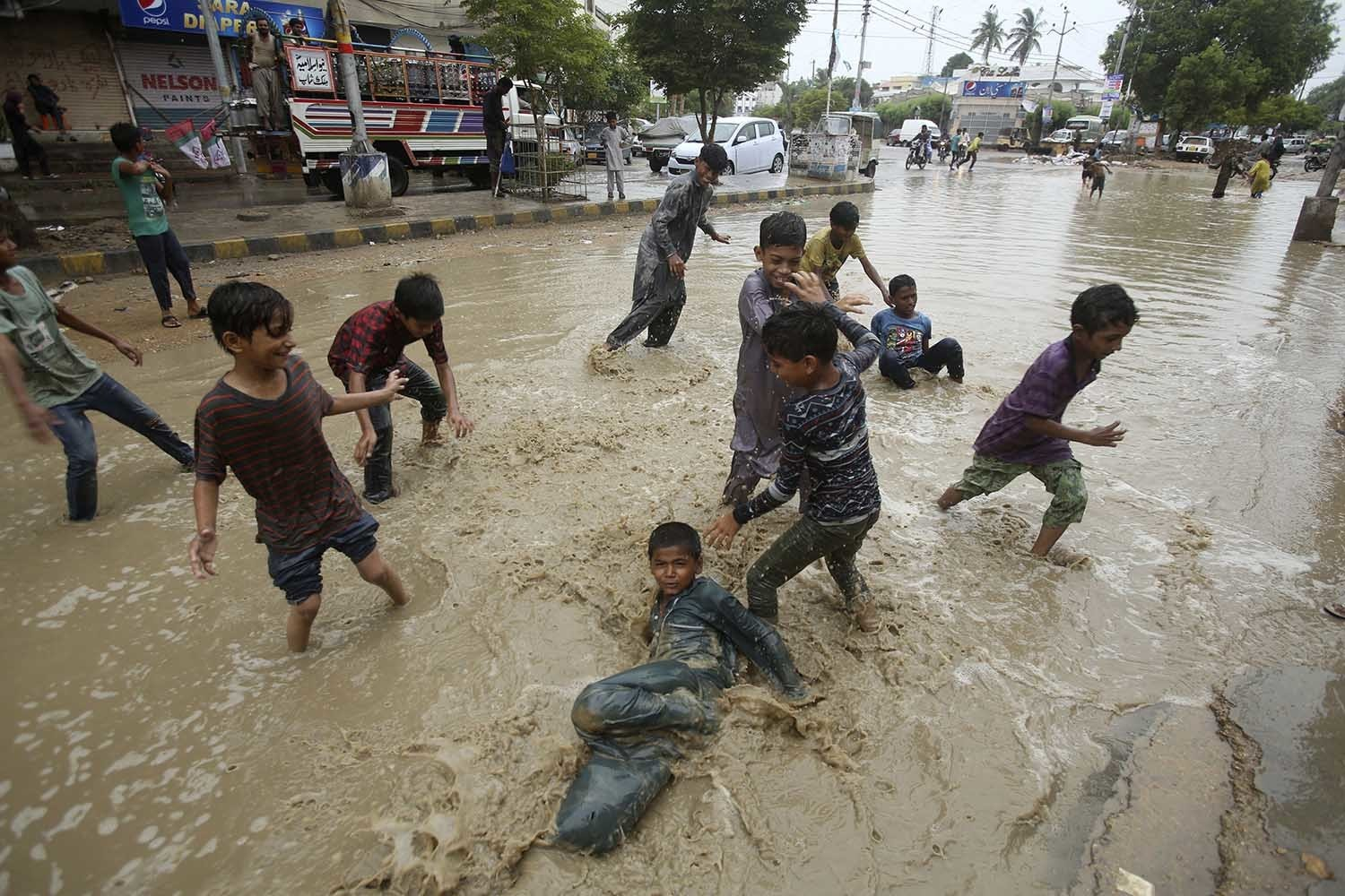 Boys play in a flooded street after a heavy rainfall in Karachi on Monday. — AP