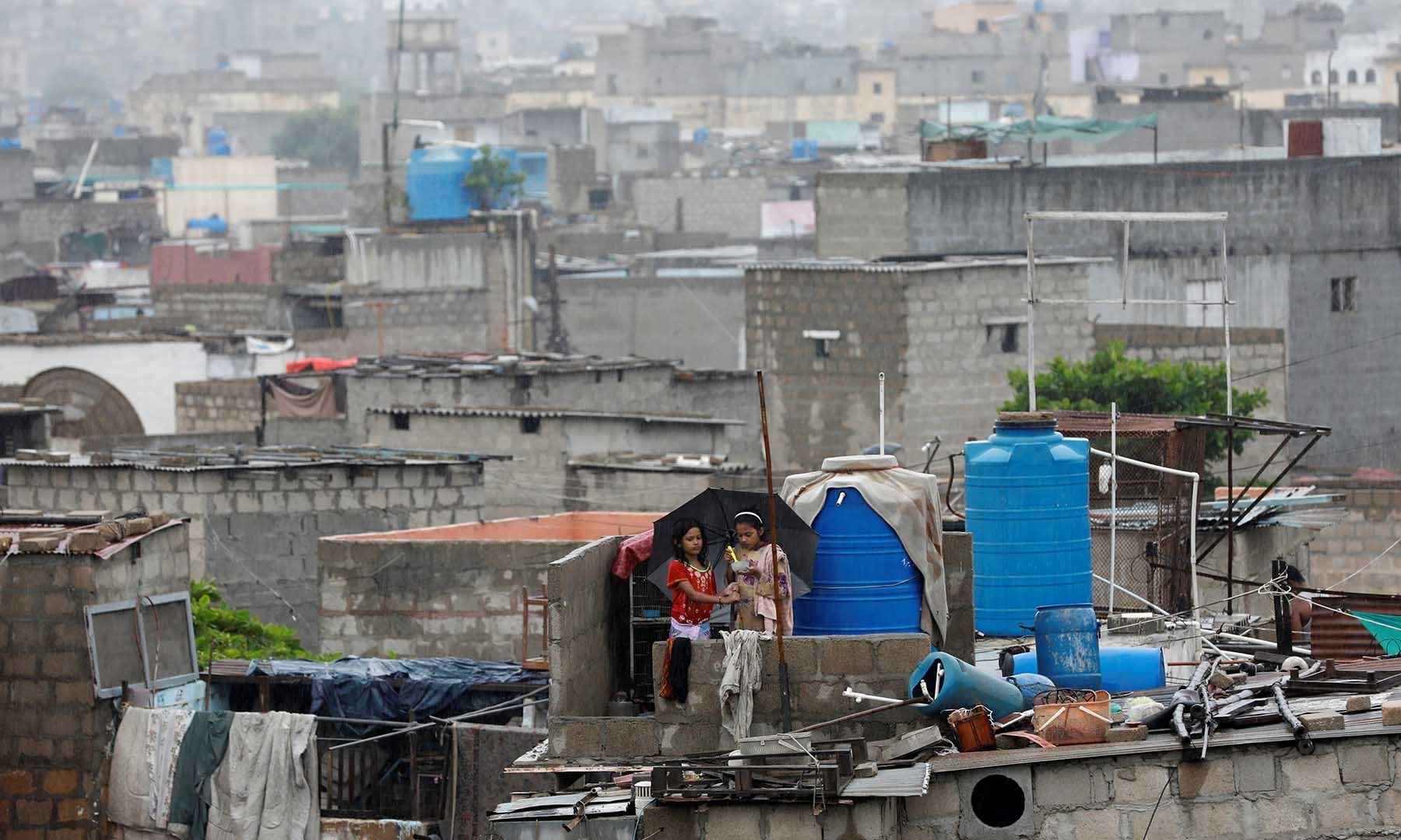 Siblings use an umbrella to avoid rain as they eat on a roof in a neighbourhood of Karachi on Monday. — Reuters