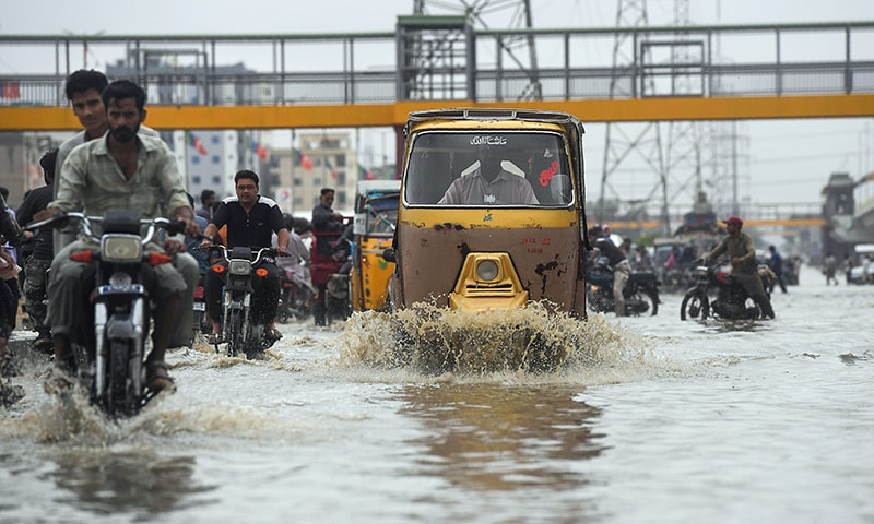 Commuters cross a flooded street during heavy monsoon rains in Karachi on Tuesday. — AFP