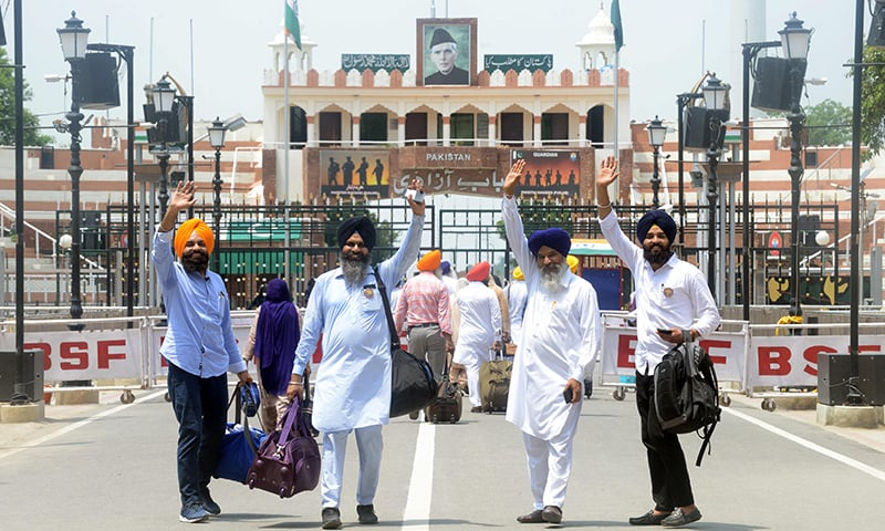 Indian Sikh pilgrims gesture as they prepare to cross the Wagah border on Tuesday. — AFP