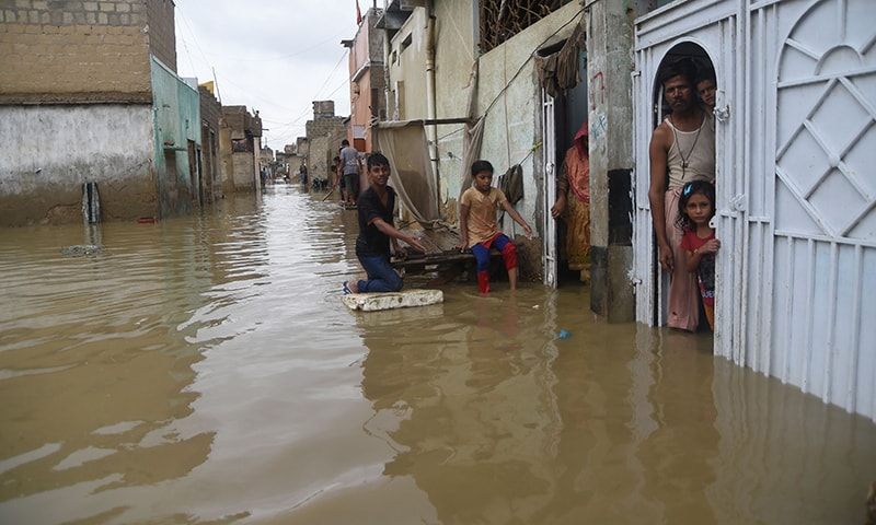 Residents look out from their houses at a flooded area during heavy monsoon rains in Karachi. — AFP