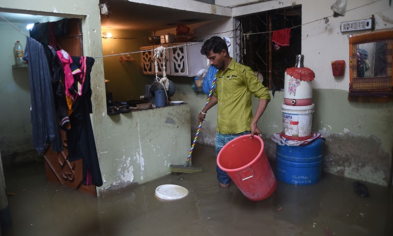 A resident tries to remove rainwater from his house during heavy monsoon rains in Karachi on July 30. — AFP