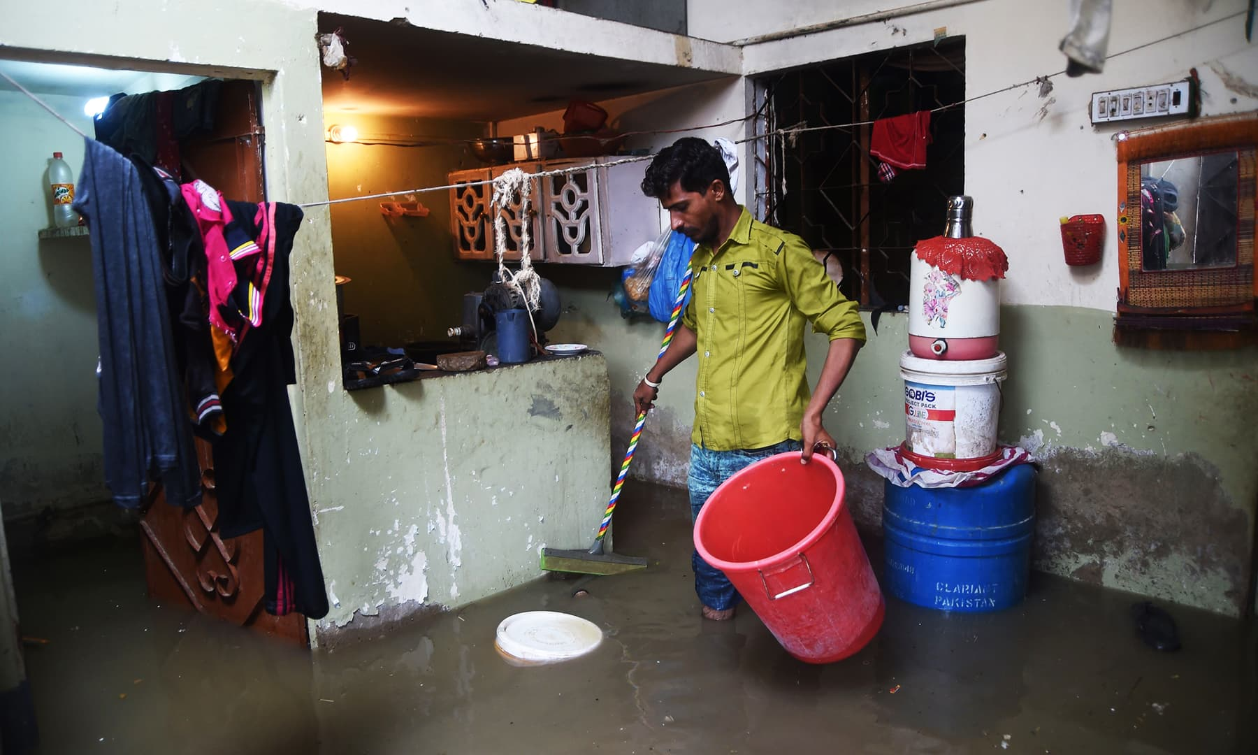 A resident tries to remove rains water from his house during heavy monsoon rains in Karachi on Tuesday. — AFP