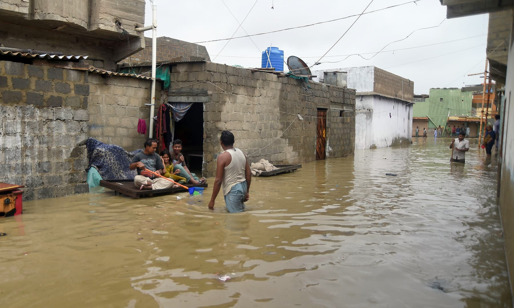 Residents sit on a cart outside their house submerge in flood waters during heavy monsoon rains in Karachi on Tuesday. — AFP