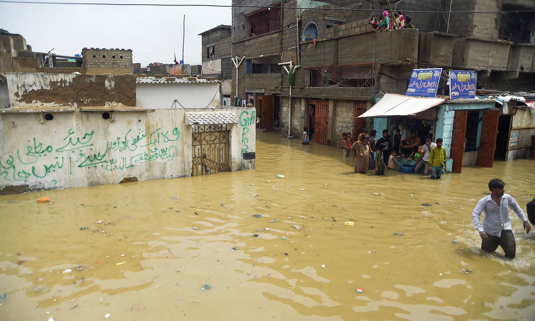 Residents in Karachi cross a flooded street on Tuesday. — AFP