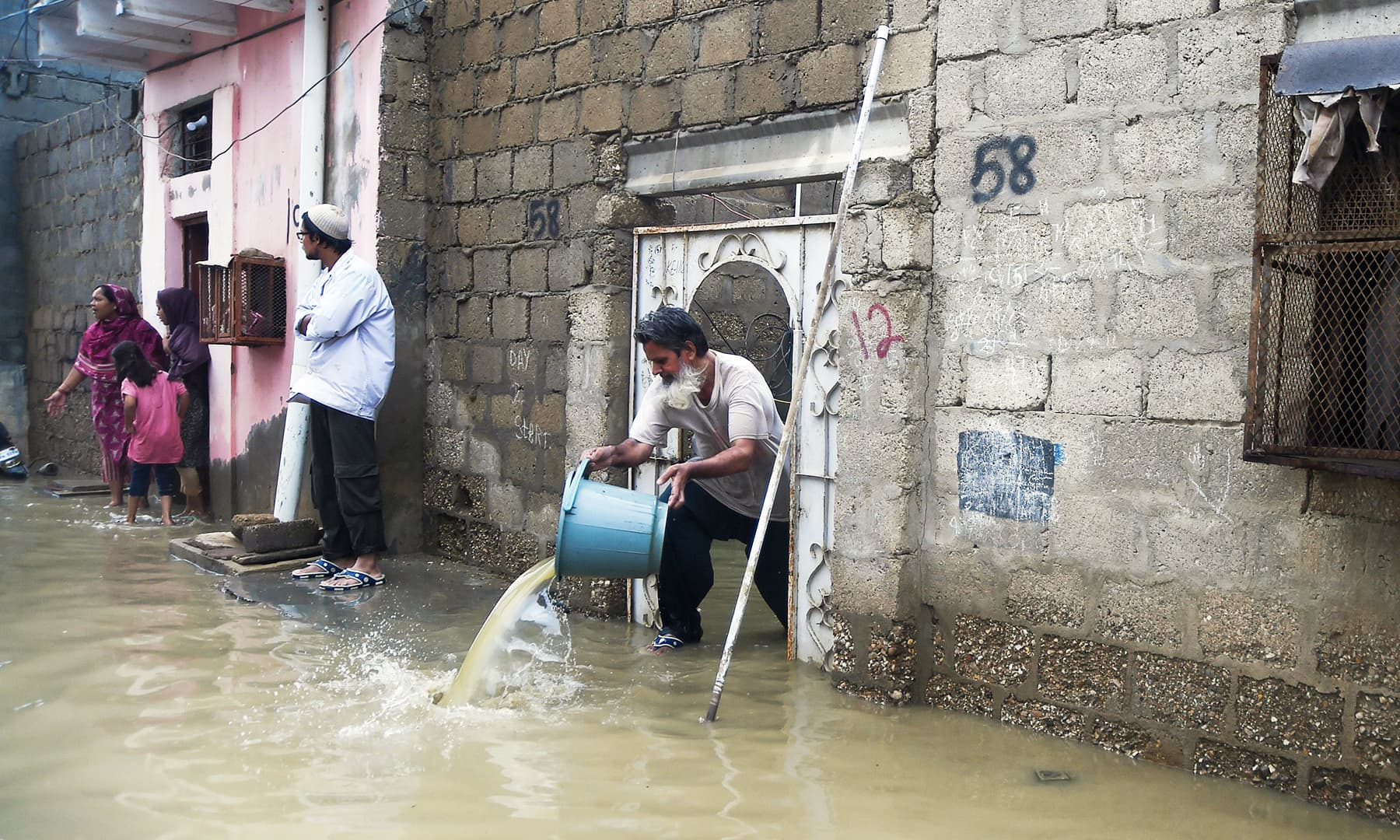 A resident removes rains water from his house in Karachi on Tuesday. — AFP