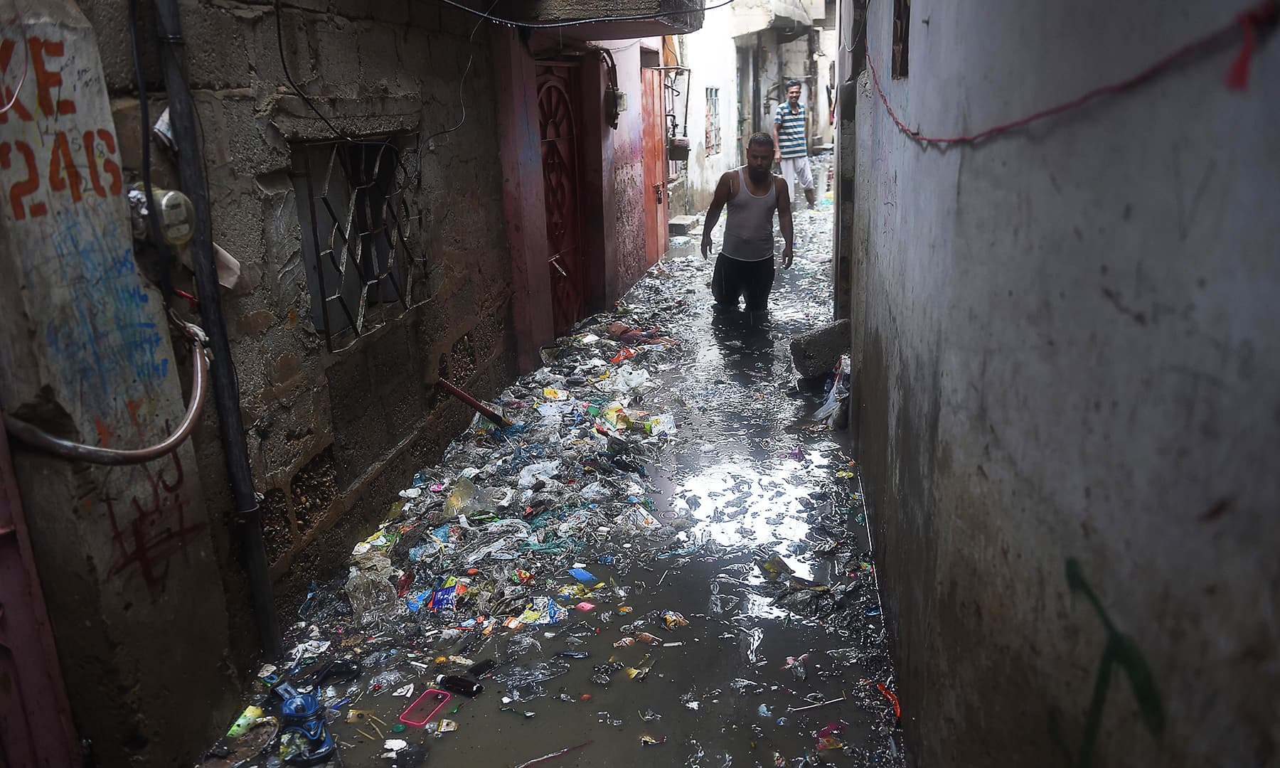 A man crosses a narrow flooded street during heavy monsoon rains in Karachi on Tuesday. — AFP