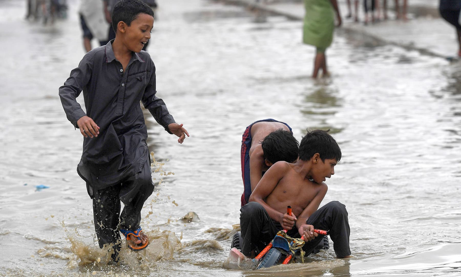 Children play in one of many flooded streets in Karachi on Tuesday. — AFP