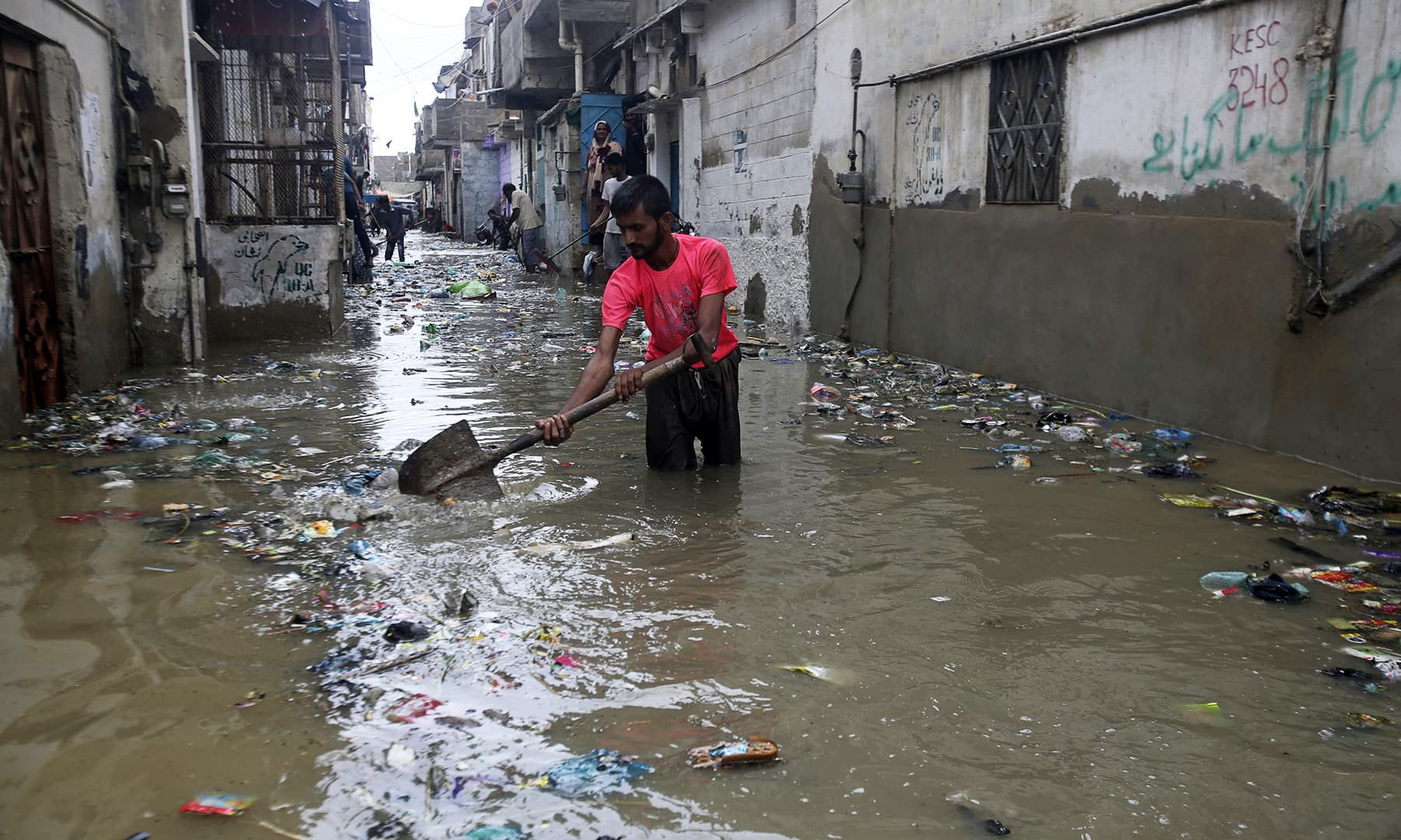 A man cleans a flooded street in Karachi on Tuesday. — AP