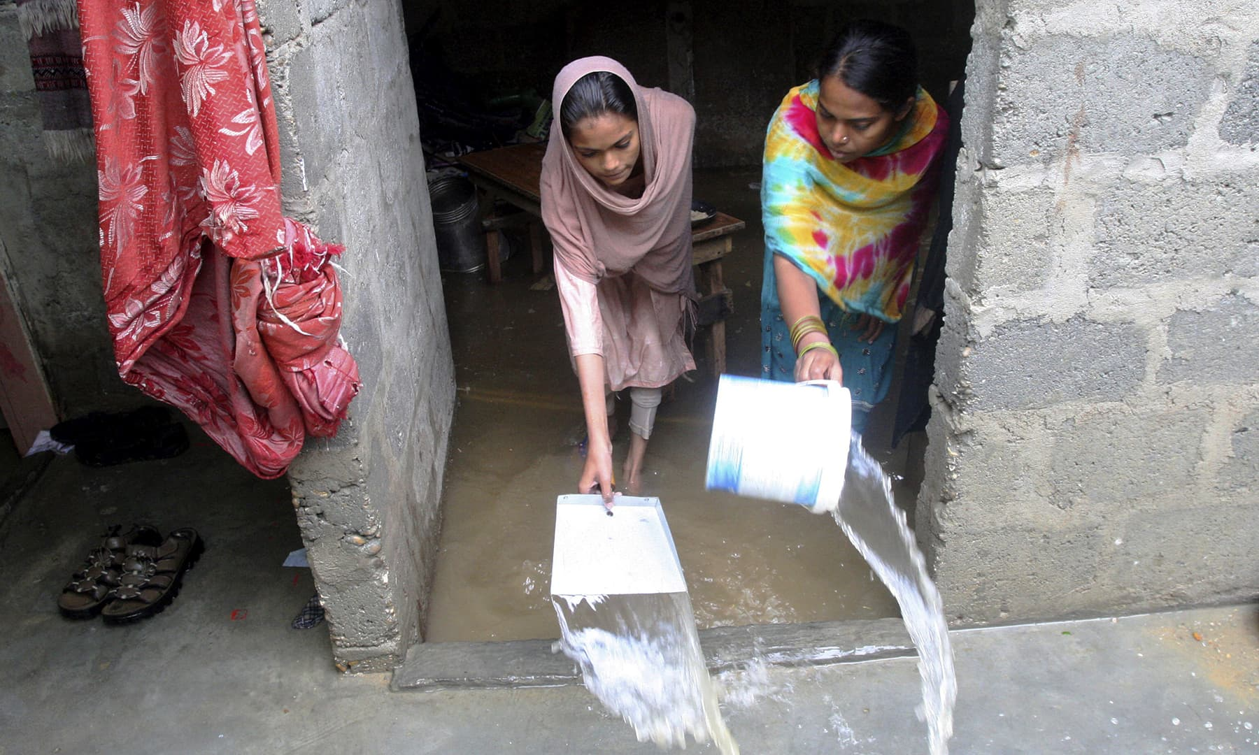 Women drain water from their house after heavy rainfall in Karachi on Tuesday. — AP