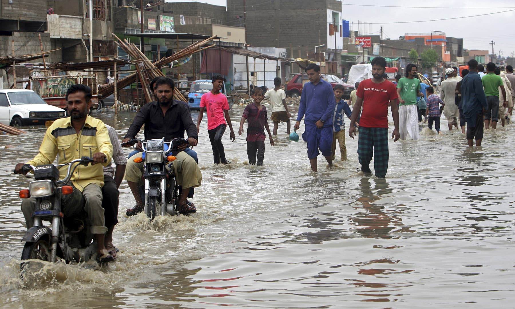 People wade through a flooded street in Karachi on Tuesday. — AP