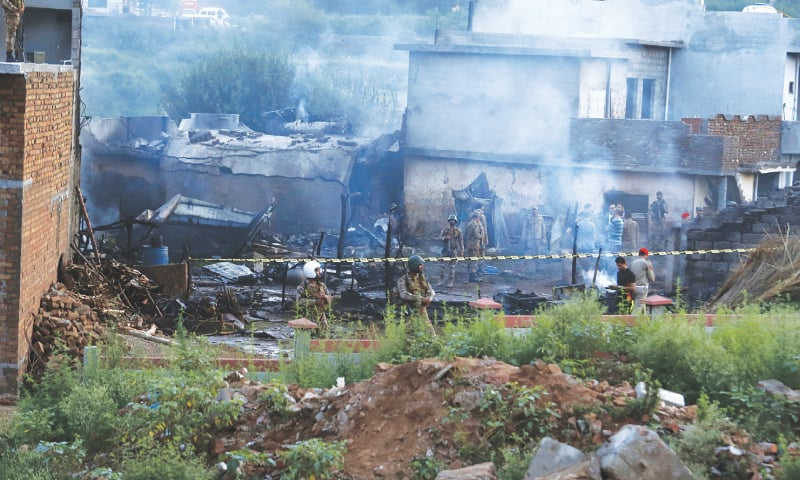 ARMY men guard the site of the plane crash in the suburbs of Rawalpindi on Tuesday. — Tanveer Shahzad/White Star