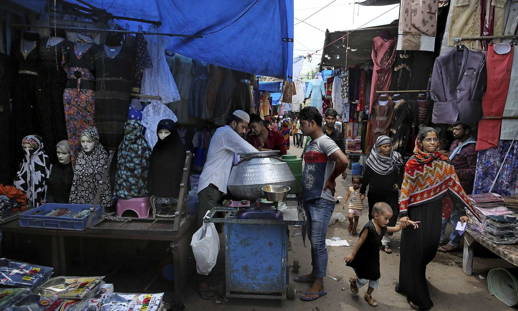 Indian Muslim women walk in a market place in New Delhi, India on Tuesday. — AP
