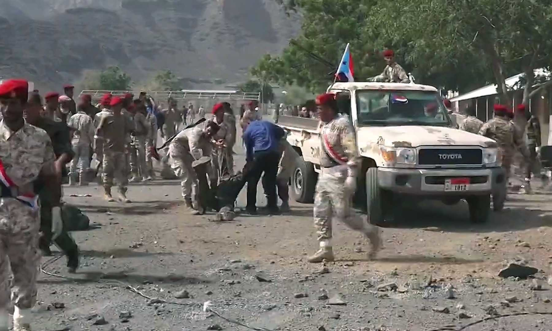 This AFPTV screen grab from a video made on August 1 shows Yemeni security forces carrying a body at the scene of a missile attack on a military camp west of Yemen's government-held second city Aden. — AFP
