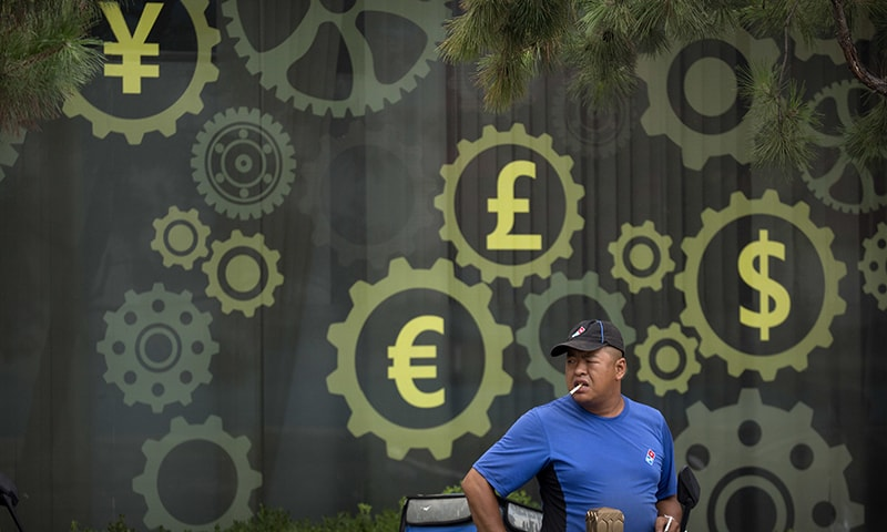 In this July 20, 2018, file photo, a deliveryman for American-based pizza chain Domino's prepares to make a delivery near a mural displaying Chinese yuan and other world currency symbols on the outside of a bank in Beijing. — AP