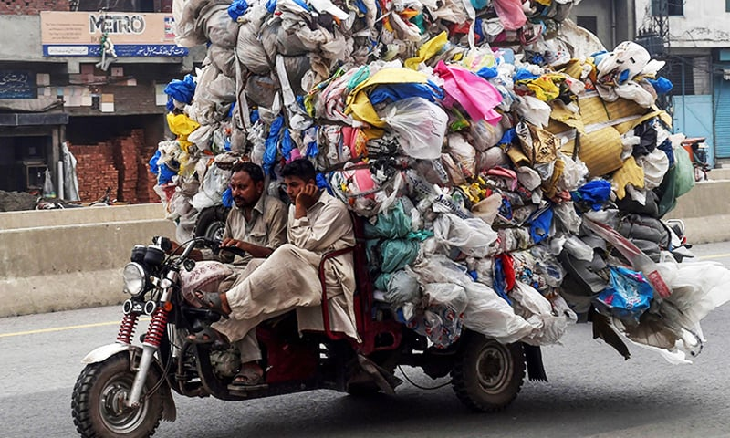 Men drive a three-wheeler loaded with used plastic bags in Lahore. — AFP