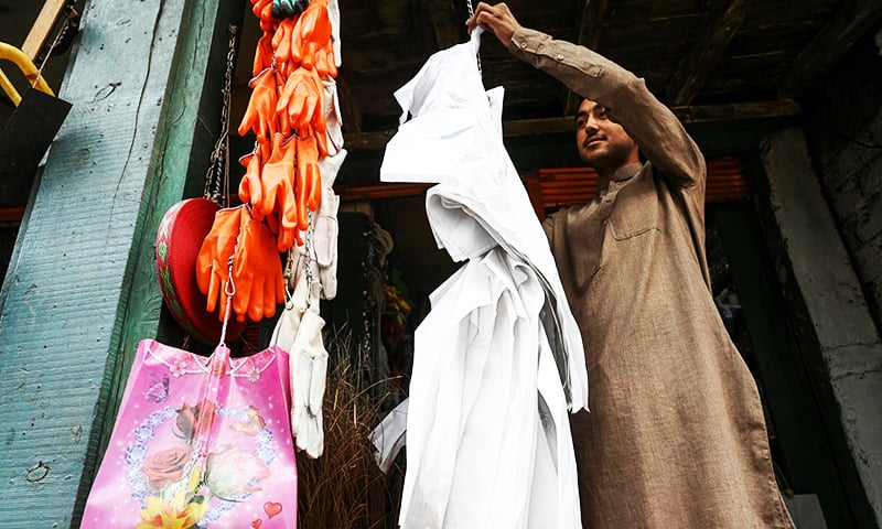 A vendor hangs biodegradable bags for sale at a market in Chitral. — AFP