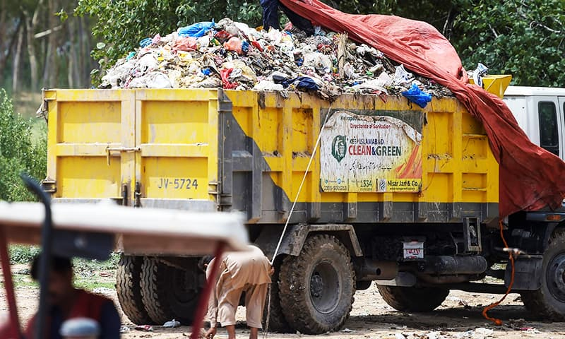 A municipal worker covers garbage at a trash site of full of plastic bags in Islamabad. — AFP