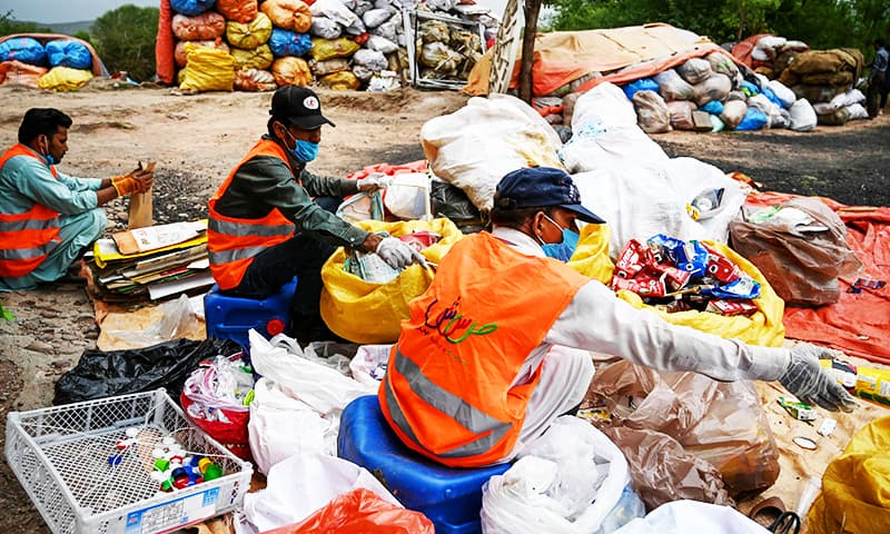 In this picture, municipal workers sort out recycling items in Islamabad. — AFP