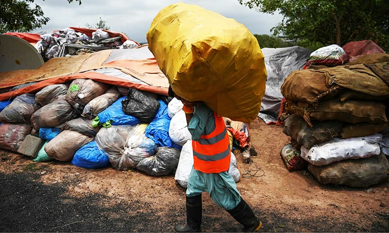 A municipal worker carries a bag of recycling items at a site in Islamabad.— AFP