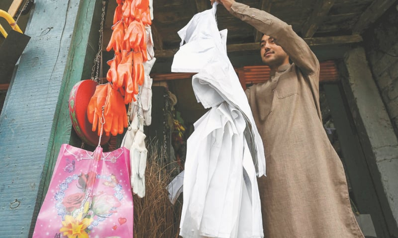 A vendor hangs biodegradable bags for sale at a market in Chitral.—AFP