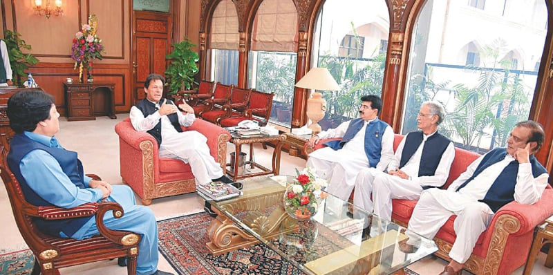 ISLAMABAD: Prime Minister Imran Khan exchanges views with Senate Chairman Sadiq Sanjrani during a meeting at the PM Office on Friday.—PPI