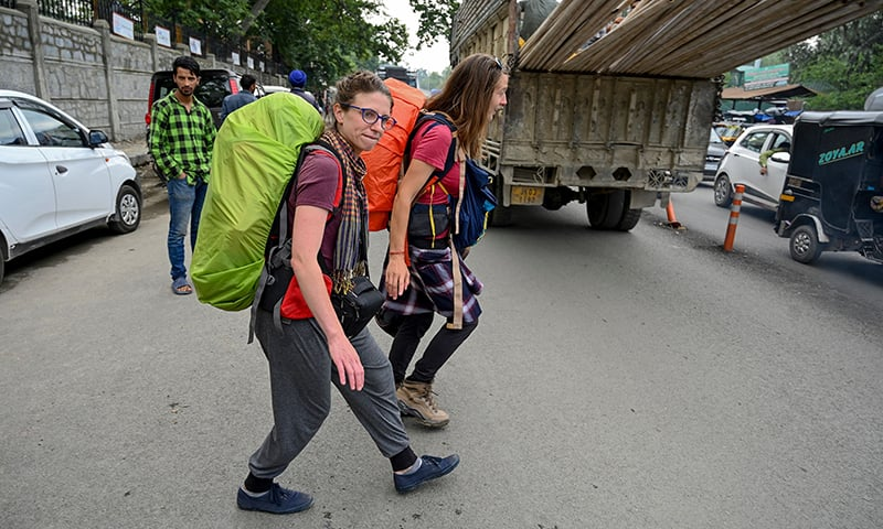 Tourists from Belgium walk on a road as they are going to leave IOK in Srinagar on Saturday. — AFP