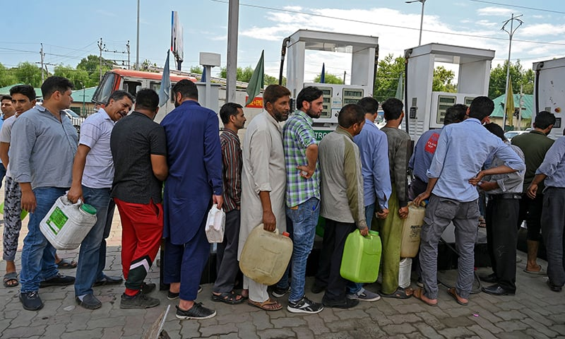 Kashmiri people stand in a queue at a petrol station in Srinagar on Saturday. — AFP