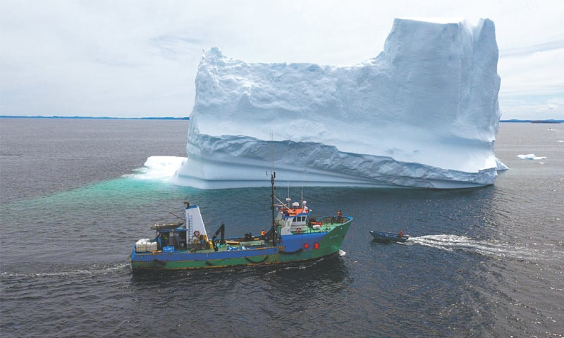 THIS photo shows the boat of Captain Edward Kean near an iceberg in Bonavista Bay in Newfoundland, Canada. — AFP