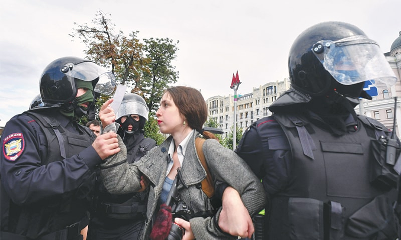 MOSCOW: Riot police detain a journalist during an unsanctioned rally calling for fair elections on Saturday.— AFP