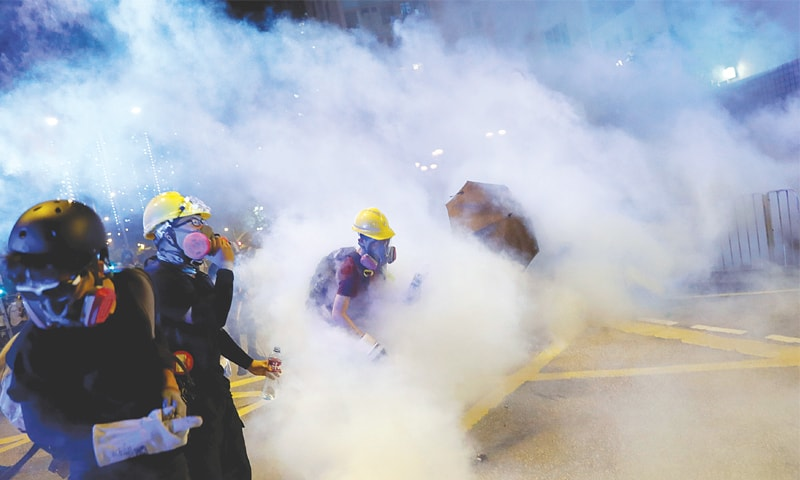 HONG KONG: Anti-extradition bill protesters walk among tear gas as they attend a march on Saturday. — Reuters