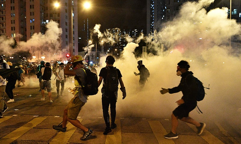 Protesters gather amid tear gas, outside of a police station in the Wong Tai Sin district of Hong Kong early on Sunday after arrested protesters were taken to the station in a police van. — AFP