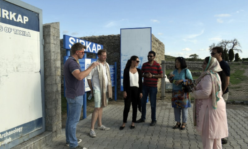 Foreign visitors being briefed on the Buddhist heritage at Sirkap near Taxila. — Dawn
